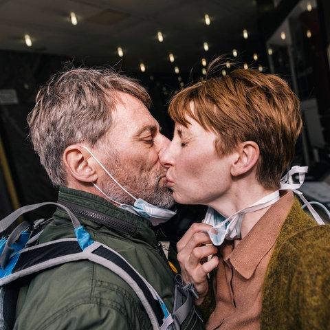 Paar küsst sich mit Maske