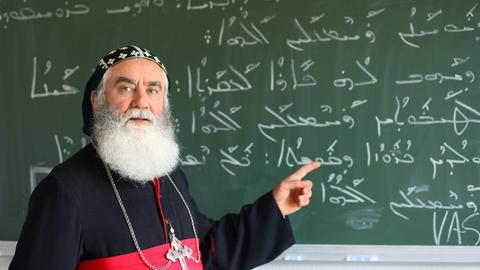 Der Erzbischof der syrisch-orthodoxen Kirche in Deutschland steht vor einer Tafel mit aramäischen Schriftzeichen.