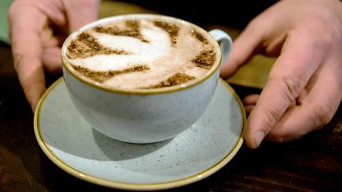 """Berlin: Nico Schack serviert im CBD-Café """"Canna"""" in einen Cappuccino."""