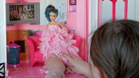 Mädchen spielt mit Puppenhaus