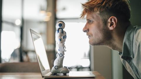 Man schaut auf Roboter der auf Laptop steht