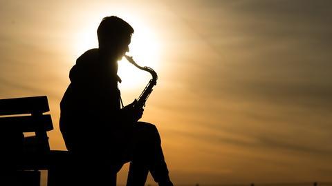 Ein Mann spielt auf dem Tempelhofer Feld in Berlin auf seinem Saxofon.