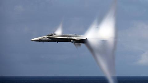 Ein Flugzeug durchbricht die Schallmauer.
