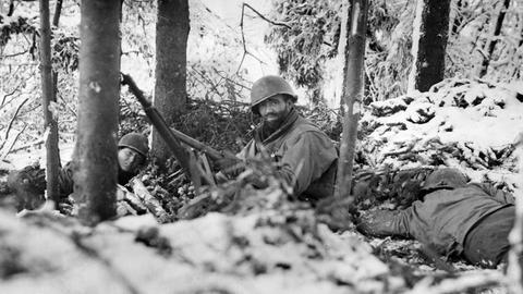 Zweiter Weltkrieg - Ardennenoffensive (WWII - Ardennenoffensive): In einem verschneiten Wald schützen sich Infanteristen der dritten US-Armee Anfang Januar 1945 vor einem feindlichen Sperrfeuer in Luxemburg