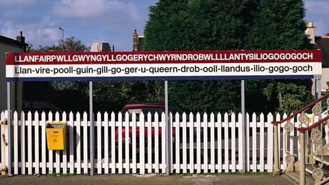 """Das Ortschild an der früheren Bahnstation von """"St. Marie am Teich der weißen Hasel neben der Stromschnelle und der Kirche St. Tysilio bei der roten Höhle"""" - so die deutsche Übersetzung des Wortungetüms, das für einen Ortsnamen aus Wales steht."""