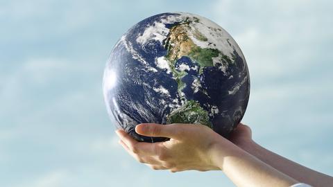 Zwei Hände halten einen Ball in Form einer Weltkugel gegen den Himmel.