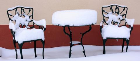 zwei Stühle und ein Tisch im Schnee