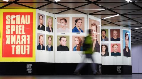 Ein Passant geht in der B-Ebene der U-Bahn-Station Willy-Brandt-Platz in Frankfurt am Main an Porträtfotos der Ensemblemitglieder des Schauspiels vorbei.