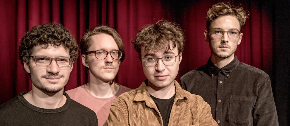 Vier junge  Männer vor einem roten Vorhang