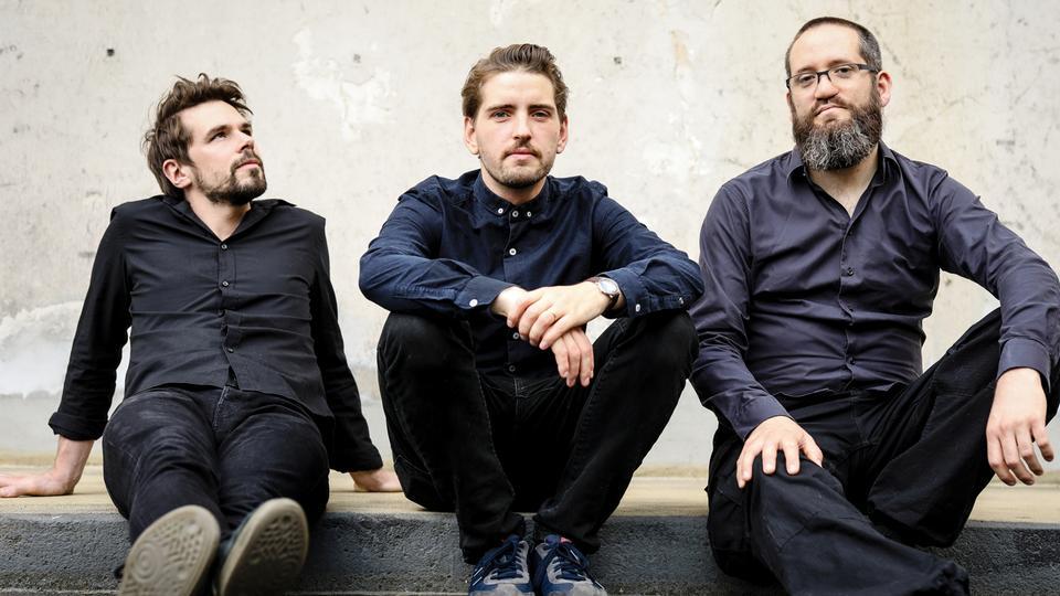 Drei Männer nebeneinander auf dem Fußboden