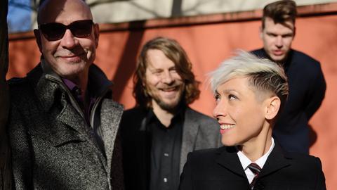 Drei Männer und eine Frau mit weißgefärbten Haaren