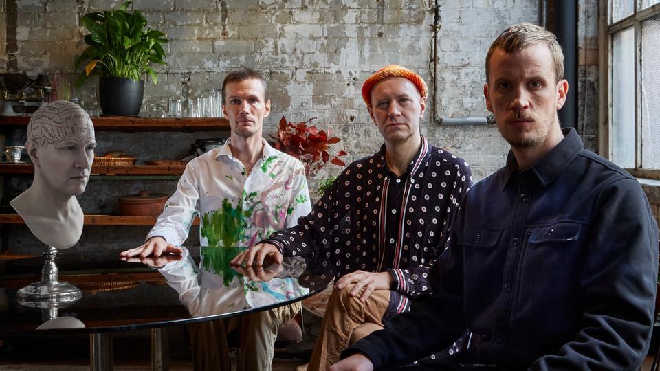 Drei Männer an einem Tisch mit einer Gipsbüste in einem Industrie-Loft