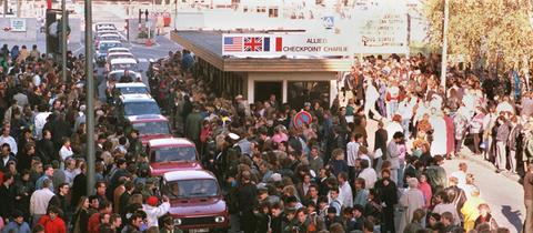 Eine Fahrzeugkolonne schiebt sich am 10.November 1989 in Richtung West-Berlin vorbei am Checkpoint Charlie.