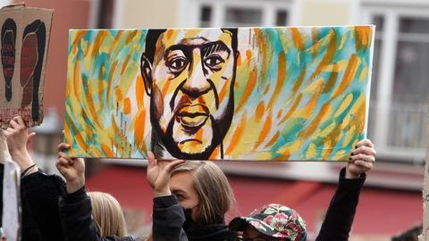 Demonstrantinnen halten ein Plakat mit einem Portrait des Opfer s Floyd in die Höhe, Hessen, Deutschland